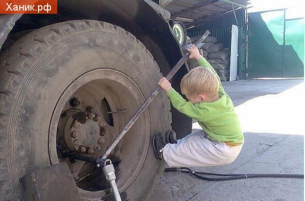 Маленький ремонтник. Карапуз пытается открутить болт колеса грузовика